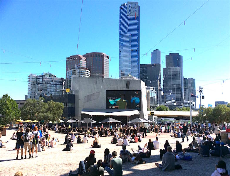 Federation Square, where hordes loll on deckchairs beneath beach umbrellas, watching the tennis on the big screen